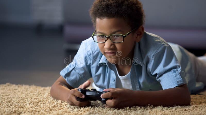 Afroer-amerikanisch Junge, der absorbedly auf neuer Videospielkonsole, Haupttätigkeit spielt stockfoto