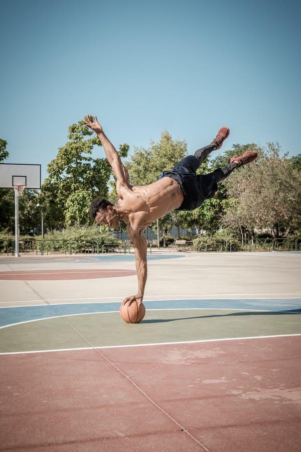 Afroer-amerikanisch junger Mann, der Straßenbasketball im Park doi spielt lizenzfreie stockfotos