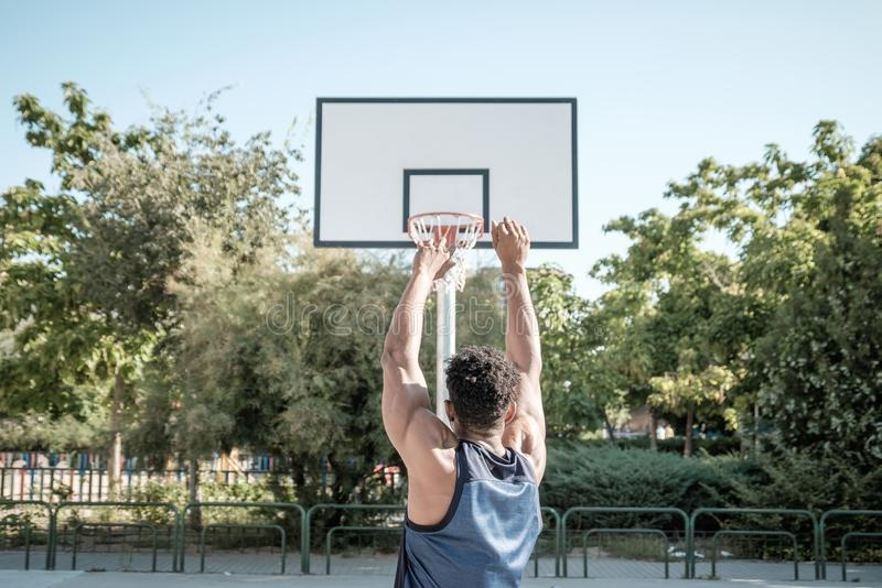 Afroer-amerikanisch junger Mann, der Straßenbasketball im Park spielt stockfotografie