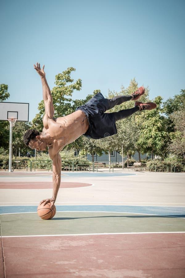 Afroer-amerikanisch junger Mann, der Straßenbasketball im Park spielt stockbilder