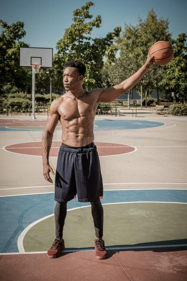Afroer-amerikanisch junger Mann, der Straßenbasketball im Park spielt lizenzfreie stockfotografie