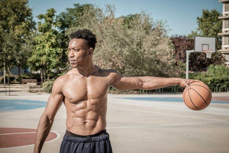 Afroer-amerikanisch junger Mann, der Straßenbasketball im Park spielt lizenzfreies stockfoto