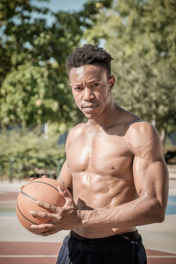 Afroer-amerikanisch junger Mann, der Straßenbasketball im Park spielt lizenzfreie stockfotos