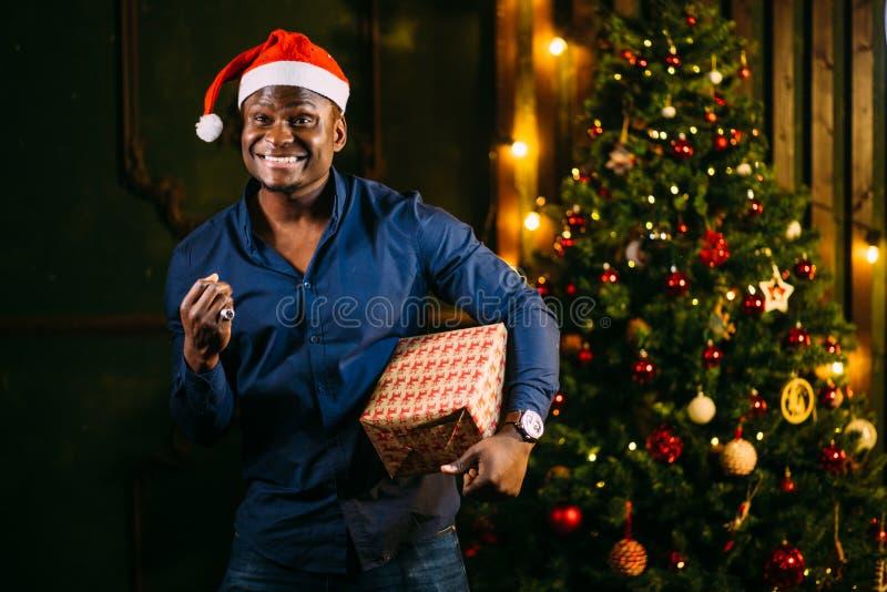 Afroer-amerikanisch Kerl mit dem reizend Lächeln, das Weihnachtsgeschenk in den Händen hält stockfotografie