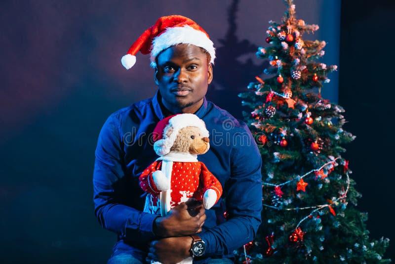Afroer-amerikanisch Kerl mit dem reizend Lächeln, das Weihnachtsgeschenk in den Händen hält lizenzfreie stockfotos