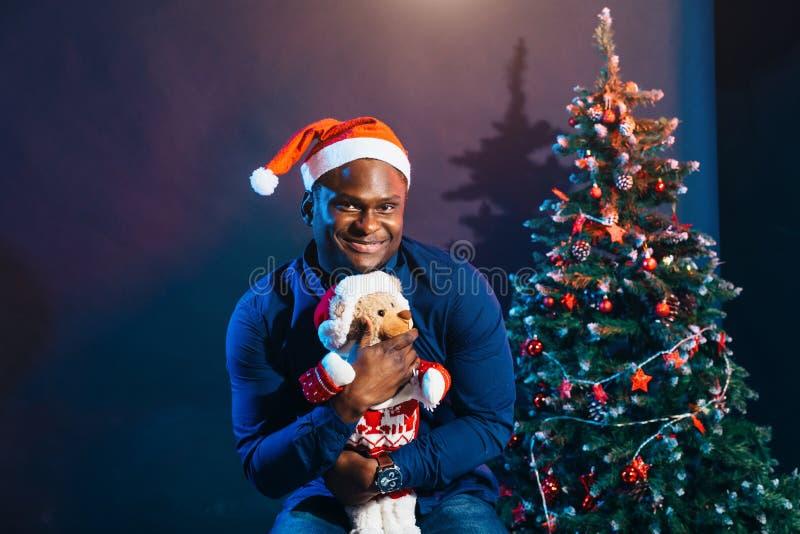 Afroer-amerikanisch Kerl mit dem reizend Lächeln, das Weihnachtsgeschenk in den Händen hält stockbilder
