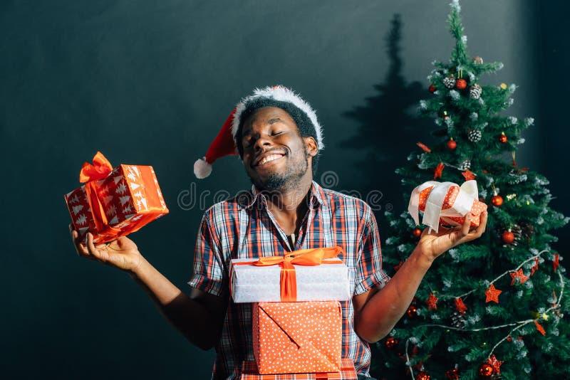 Afroer-amerikanisch Kerl mit dem reizend Lächeln, das Weihnachtsgeschenk in den Händen hält stockbild