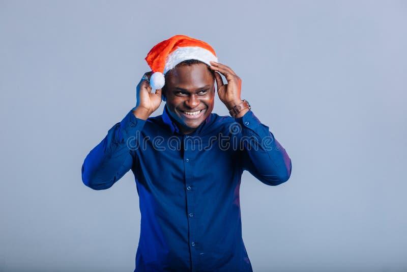 Afroer-amerikanisch Kerl mit dem reizend Lächeln, das Weihnachtsgeschenk in den Händen hält lizenzfreies stockbild