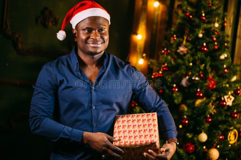 Afroer-amerikanisch Kerl mit dem reizend Lächeln, das Weihnachtsgeschenk in den Händen hält stockfoto