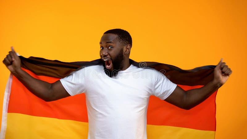Afroer-amerikanisch Mann, der die deutsche Flagge, jubelnd f?r Lieblingssportteamsieg h?lt zu lizenzfreie stockbilder