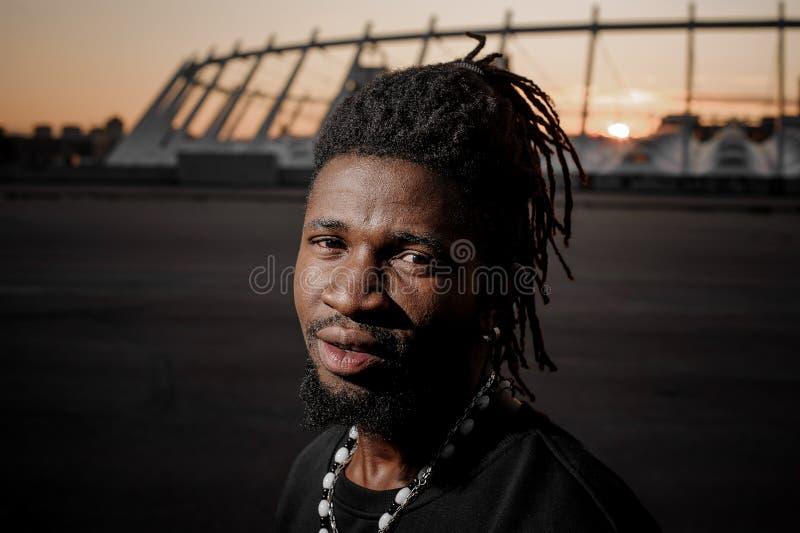 Afroer-amerikanisch Mann mit Dreadlocks mit nachdenklichem Blick und dem Stahlearing stockbild