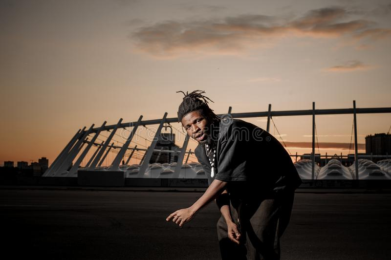 Afroer-amerikanisch Mann mit Dreadlocks verschiebt sich auf dem Hintergrund des Sonnenuntergangs lizenzfreie stockfotos