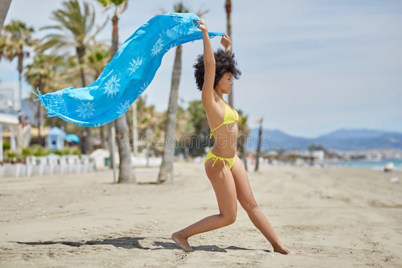 Afroes-amerikanisch Frauentanzen auf dem Strand, der Schal hält lizenzfreies stockbild