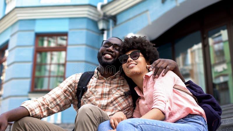 Afroes-amerikanisch Studentenpaarumarmen, sitzend auf Hochschulgebäudetreppe stockbild