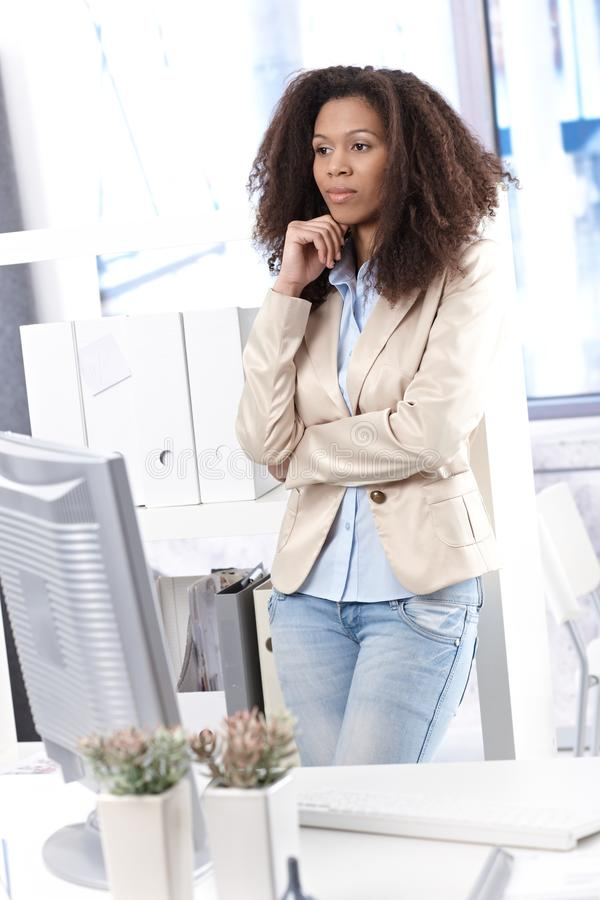 Afrogeschäftsfrau, die im Büro denkt stockbild