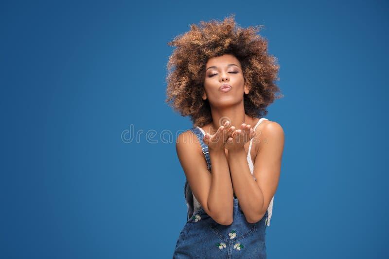 Afromädchen, das Küsse zur Kamera schickt lizenzfreies stockbild