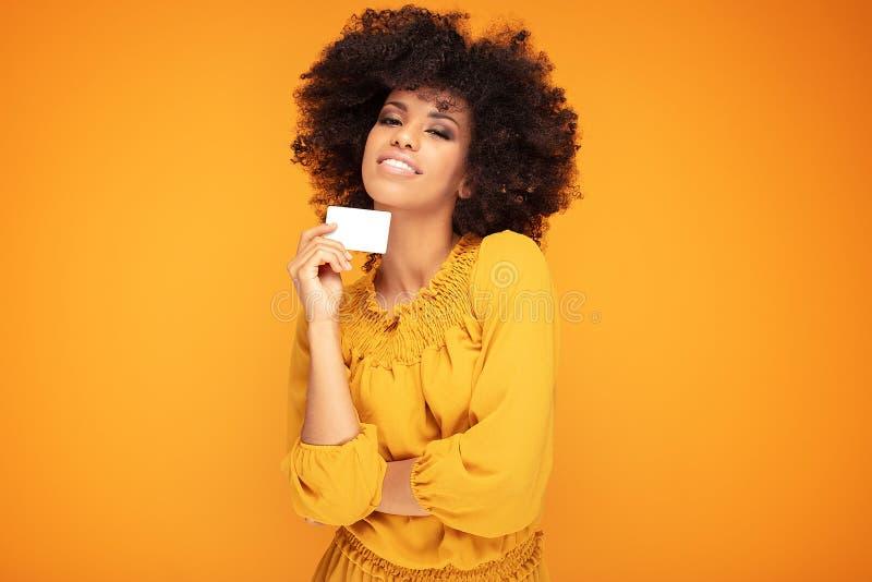 Afromädchen-Holdingkreditkarte in der Hand lizenzfreie stockfotos