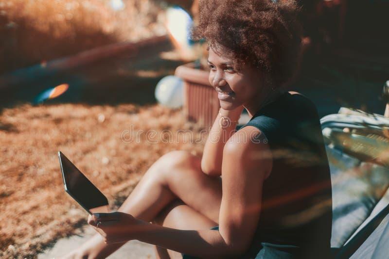 Afromädchen im Garten mit digitaler Tablette lizenzfreies stockbild