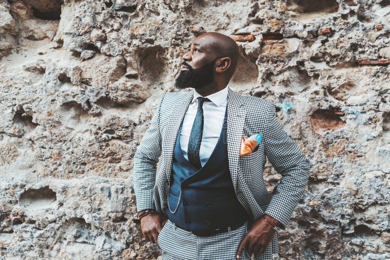 Afromens in elegant kostuum dichtbij een muur royalty-vrije stock foto