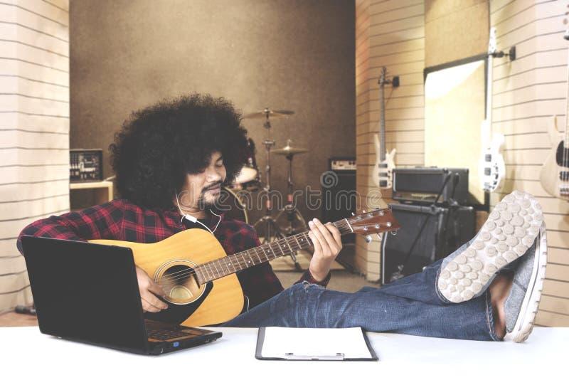 Afromens het spelen gitaar met laptop op lijst royalty-vrije stock foto