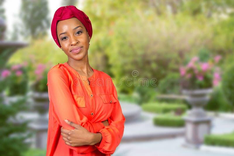 Afroschönheit, die ein rotes Kopftuch trägt stockfoto