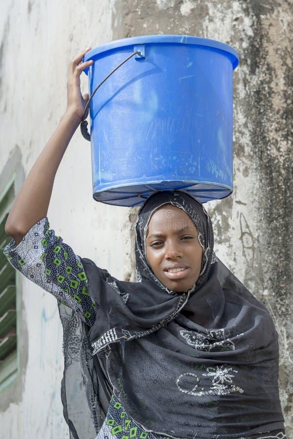 Afroschönheit, die einen Eimer Wasser in einer Schnecke trägt stockfotografie