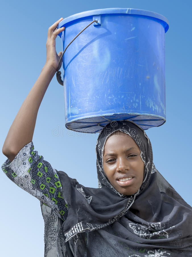 Afroschönheit, die einen Eimer Wasser trägt lizenzfreie stockfotos