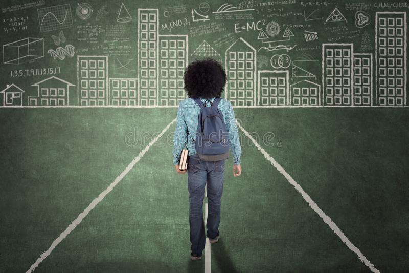 AfroStudent, der auf eine Tafel geht stockbilder