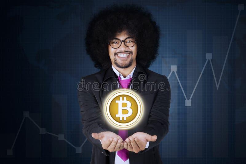 Afrozakenman die bitcoin op zijn handen tonen royalty-vrije stock afbeeldingen
