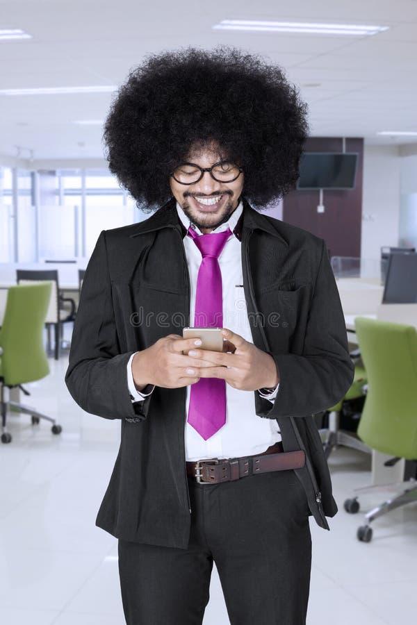 Afrozakenman die tekstberichten verzenden royalty-vrije stock afbeeldingen