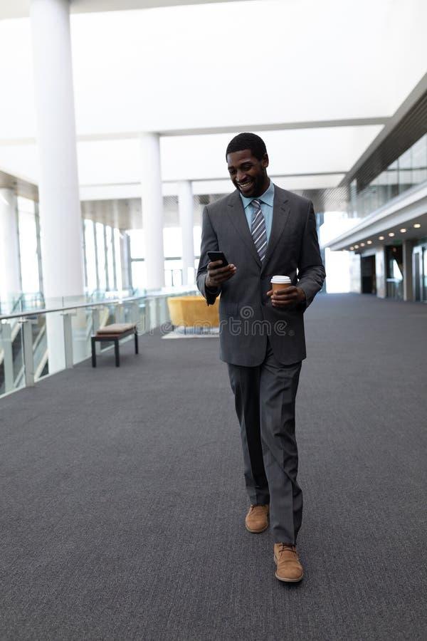 Afrrican-αμερικανικός επιχειρηματίας με το φλυτζάνι καφέ που χρησιμοποιεί το κινητό τηλέφωνο περπατώντας στην αρχή στοκ εικόνα με δικαίωμα ελεύθερης χρήσης