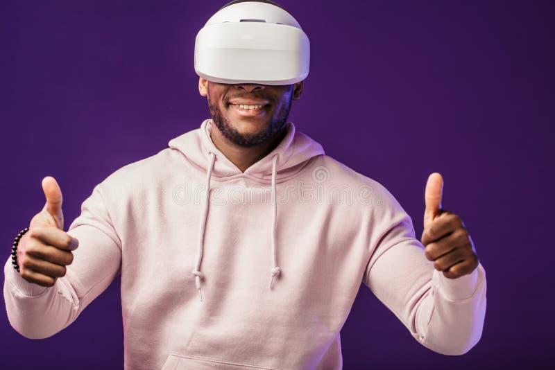 Afrykański mężczyzna jest ubranym rzeczywistość wirtualna gogle na ciemnym purpurowym tle fotografia royalty free