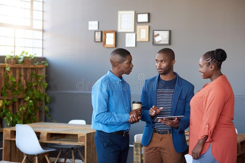 Afrykańscy biznesmeni dyskutuje cyfrowego obieg w biurze zdjęcia stock