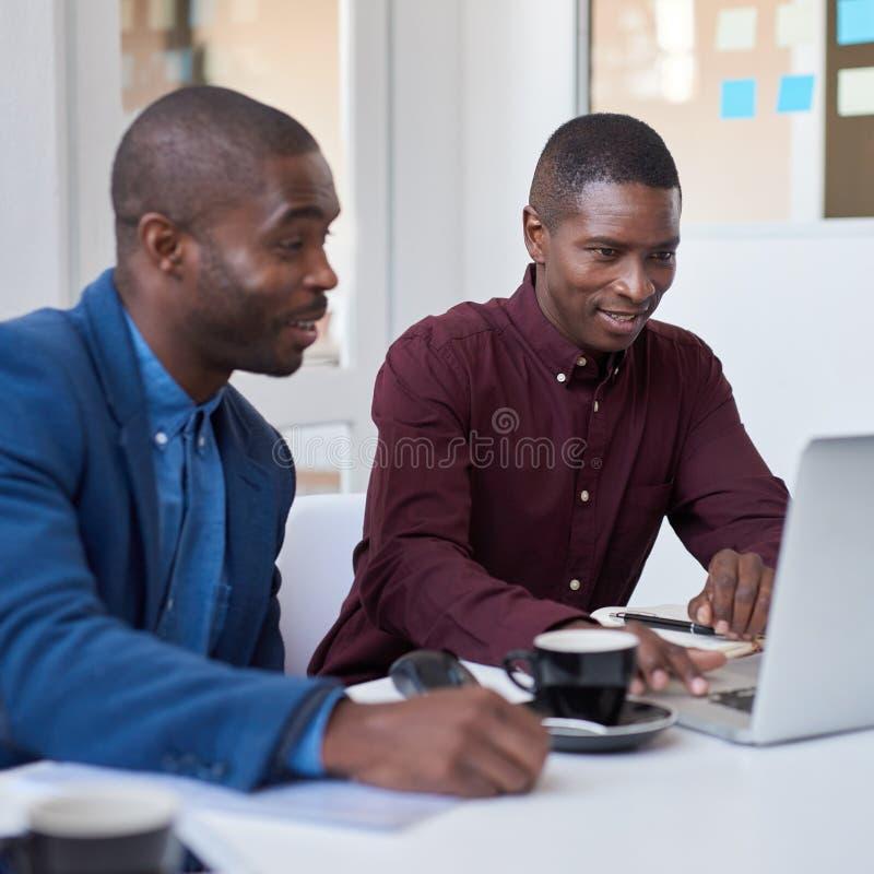 Afrykańscy biznesmeni pracuje na laptopie w białym biurze zdjęcie royalty free