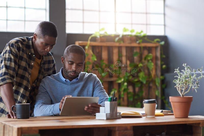 Afrykańscy biznesmeni przy pracą na pastylce w biurze obraz stock