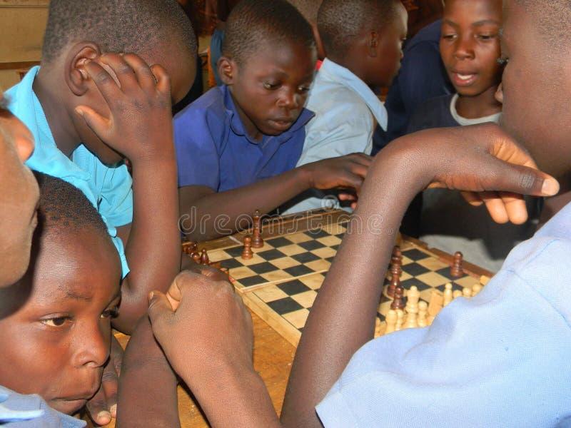 Afrykańscy dziecko w wieku szkolnym bawić się szachy zdjęcia stock