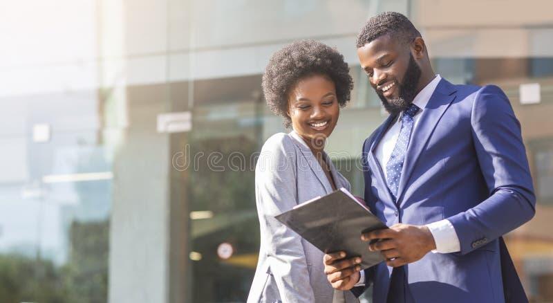 Afrykańscy partnery biznesowi czyta pieniężnych raporty outdoors fotografia stock