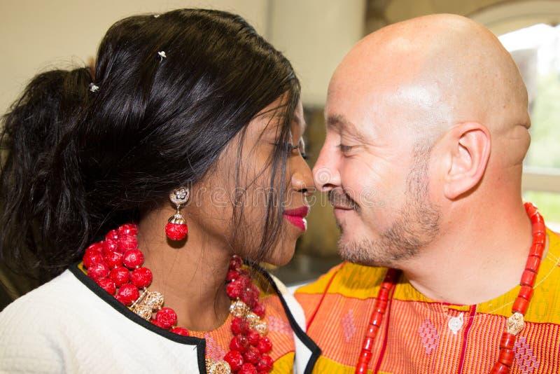 Afrykańska Ślubna panna młoda w tradycyjnym stroju z caucasian fornala buziakiem zdjęcie stock