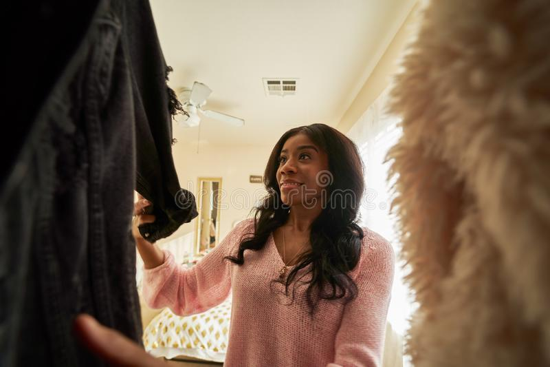 Afrykańska amerykanka patrząca przez szafę na ubrania obraz royalty free