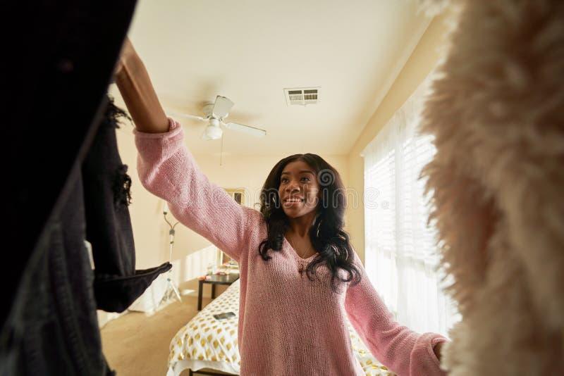 Afrykańska amerykanka patrząca przez szafę na ubrania zdjęcia royalty free