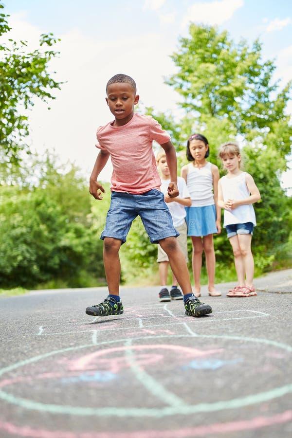 Afrykańska chłopiec bawić się hopscotch z przyjaciółmi obrazy stock