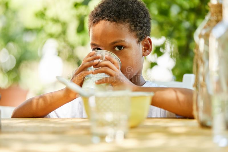 Afrykańska chłopiec pije szkło mleko fotografia royalty free