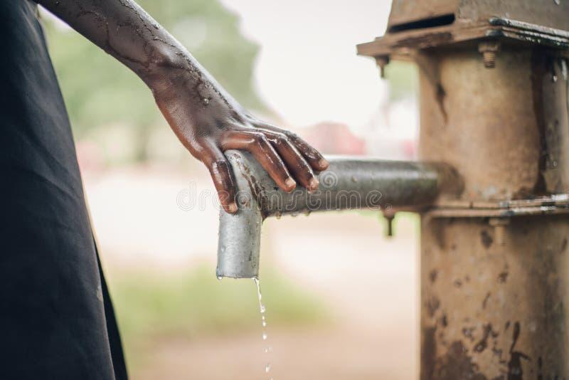 Afrykańska dzieci miejsc ręka na spout wodnej fontanny pompy narządzanie nieść wodę obraz royalty free