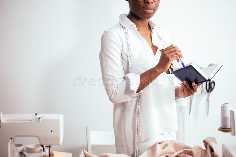 Afrykańska dziewczyny szwaczka robi notatkom przy notatnikiem projektanta rysunku nakreślenia obraz stock