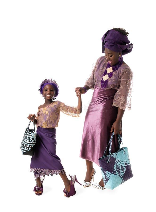 Afrykańska kobieta i urocza mała dziewczynka w tradycyjnej odzieży z duży ciężar torbami odosobniony obraz stock