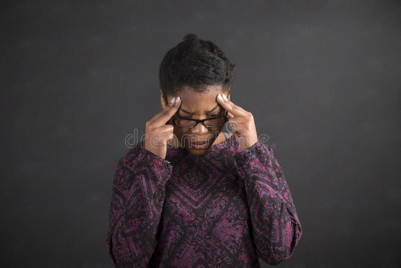 Afrykańska kobieta myśleć na blackboard tle z palcami na świątyniach fotografia stock