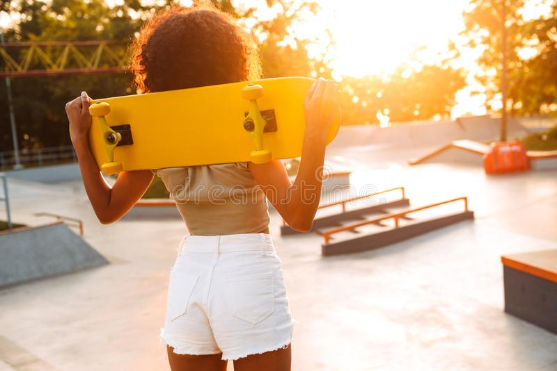 Afrykańska kobieta outdoors z deskorolka obraz stock