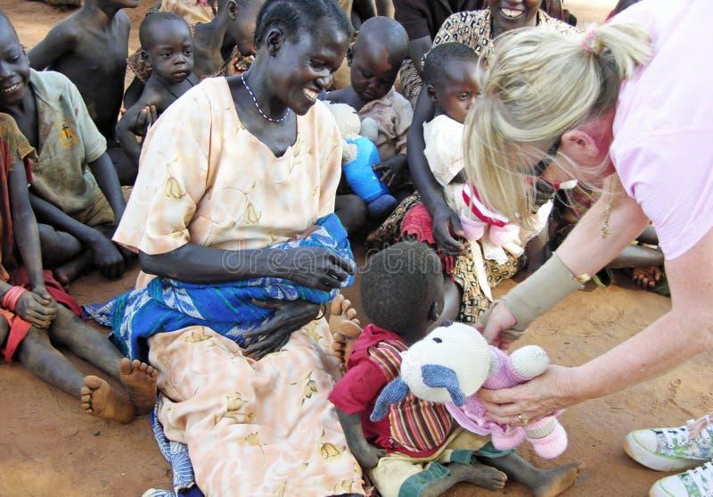 Afrykańska kobieta wypełniał z radością gdy jej dziecka dziecku oferują prezent obraz stock