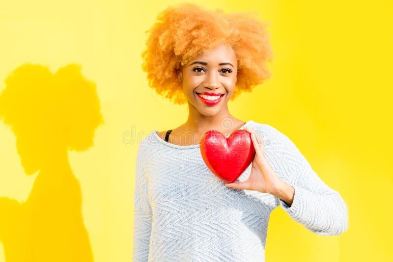 Afrykańska kobieta z sercem na żółtym tle zdjęcie royalty free