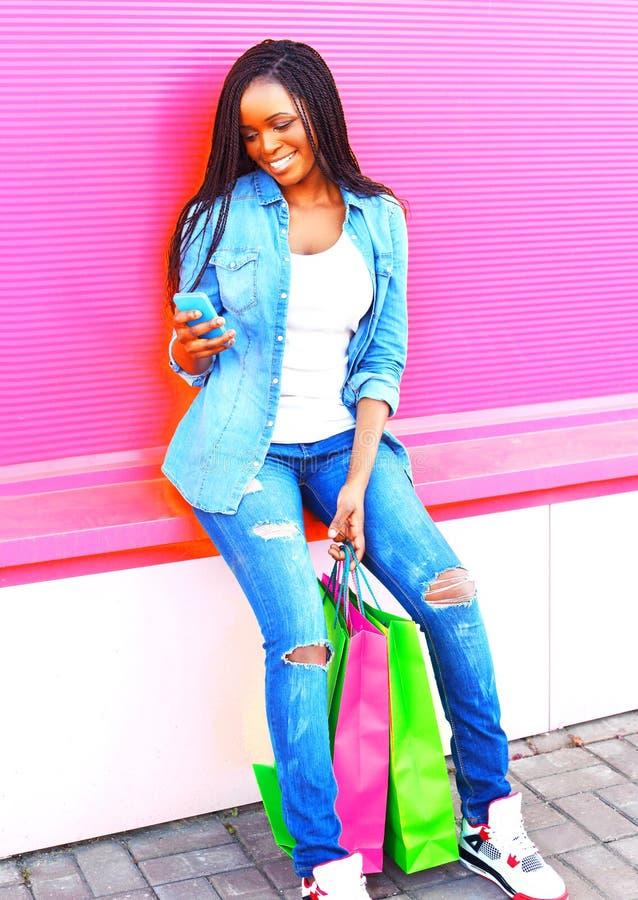 Afrykańska kobieta z torba na zakupy używać smartphone w mieście obraz royalty free
